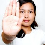 young woman in white shirt holding up hand defensively to back off