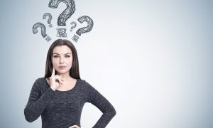 young woman in dark gray sweater with curious face and question marks