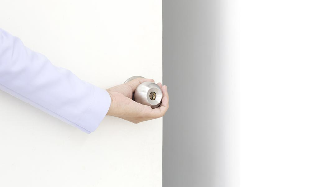 hand opening a white door with silver door knob