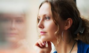 worried brunette woman looking outside the window