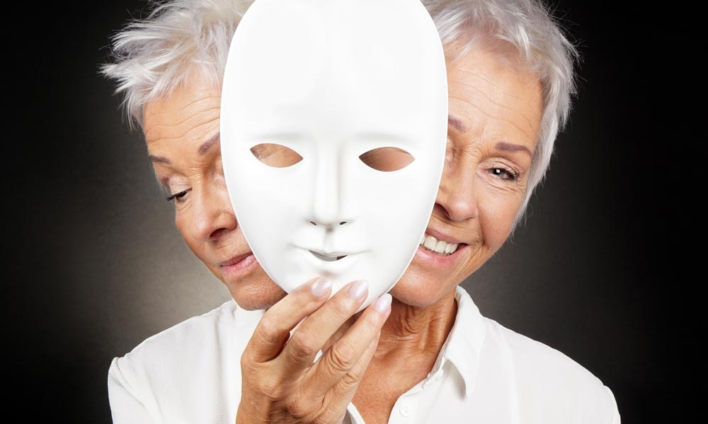 two-faced older woman both sad and happy holds a mask