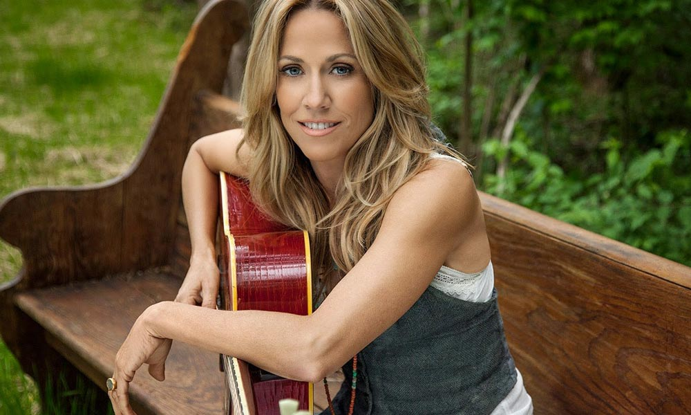 sheryl crow smiling and sitting on a wooden bench with an acoustic guitar