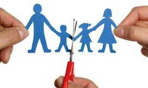 scissors separating a family made out of paper due to divorce