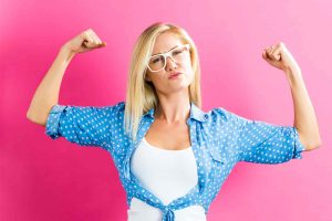 blonde woman feeling empowered flexing muscles with both arms