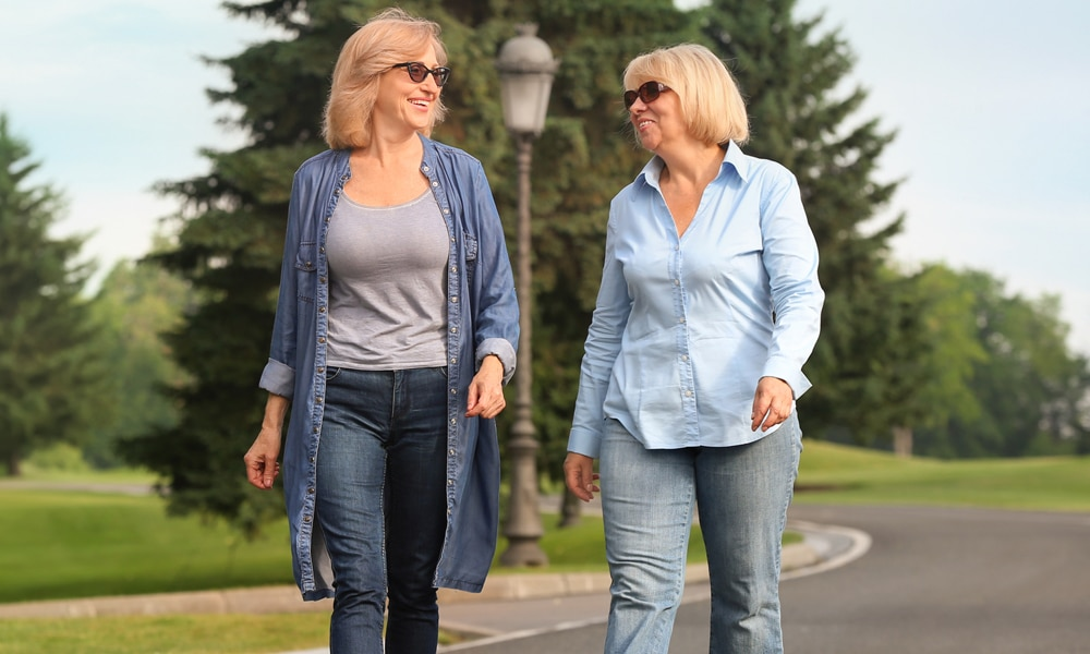 two women walking on the street smiling