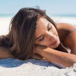 woman sun tanning on beach